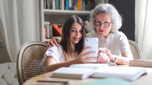 photo of woman showing her cellphone to her grandmother